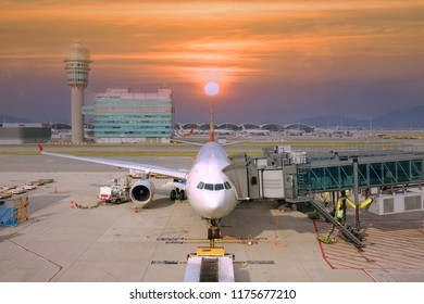 The airplane at departure & ariival gate in the Airport with beautiful sky sunset .