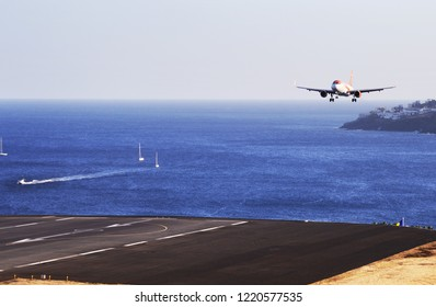 Airplane easyJet  Airbus flying to the airport runway. The Commercial jet aeroplane started the landing gear system for landing.. Airport Funchal, Madeira, Portugal. Atlantic Ocean. August 12, 2018.