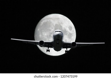 Airplane flies in front of full moon