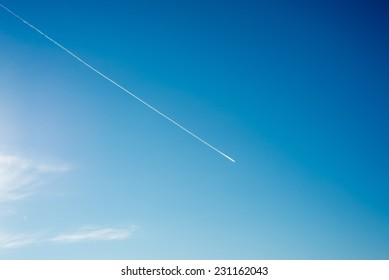airplane flies in white clouds in a blue sky and leaving trail.
