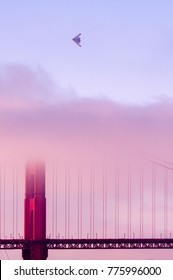 Airplane flighing above the Golden Gate on a foggy day