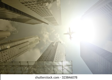 Airplane flight over modern building at afternoon.