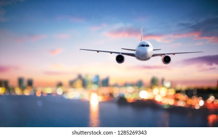 Airplane In Flight At Twilight With Blurred Cityscape