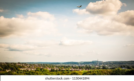 An airplane flights over Salisbury viewed from the Old Sarum, the site of the earliest settlement of Salisbury in England. In the picture is the the famous Salisbury cathedral, Britain's tallest spire