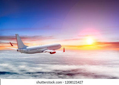 Airplane flying above clouds at colorful sunset. Lens flare effect.