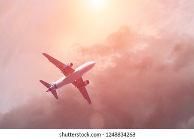 Airplane flying above clouds in dramatic sunset light. Travel and transportation concept.