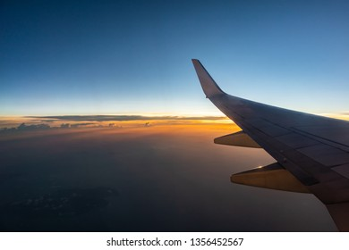 Airplane flying above the clouds at sunset.