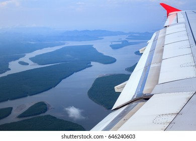 Airplane flying above mangroves forest, view from airplane window