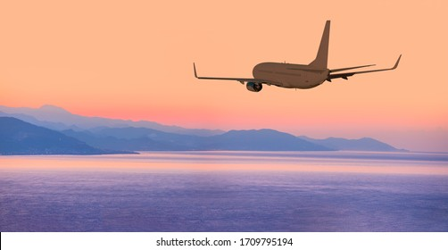Airplane flying above tropical sea at amazing sunset