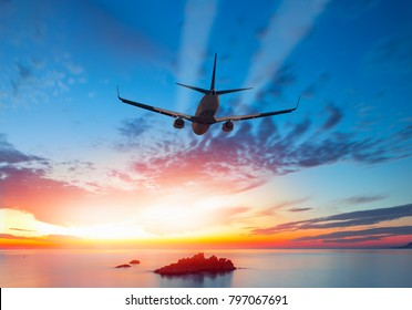 Airplane flying above tropical sea at sunset