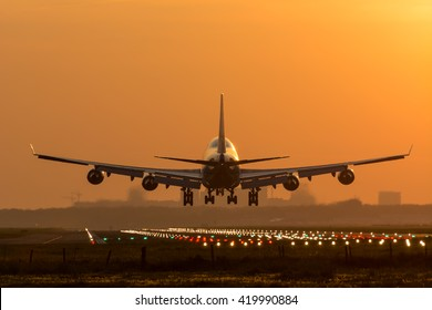 Airplane is flying to the airport, rising sun at the background.