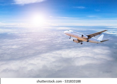 airplane flying away in to sky high altitude above the white clouds