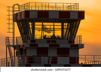 Airplane flying behind airport control tower during sunset. Passnger plane take off view through ATC tower glasses.