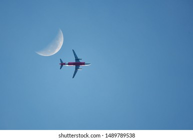 Airplane flying in the blue sky background and the moon in the morning.