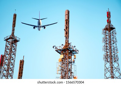 Airplane flying in the blue sky with communication antenna in the foreground.