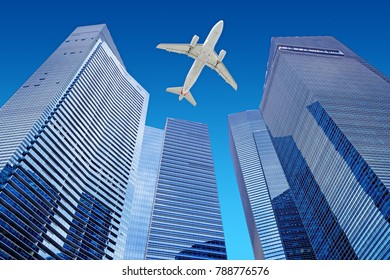 airplane flying in the blue sky over skyscrapers of a financial district