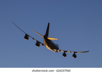 Airplane flying in the blue sky. Sun glare on the aireplane below. Boeing 747-8f.