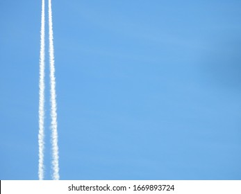 Airplane flying in the clear blue sky and contrail against, Engine exhaust contrails forming behind,  Jet contrails or trails over blue sky and clouds.