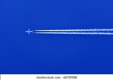 A airplane is flying from east to west. The sky is perfectly blue.