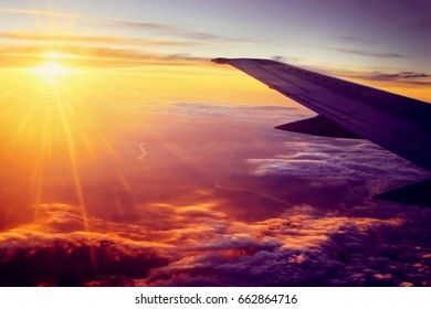 Airplane flying high above the clouds at sunset. Nature background.