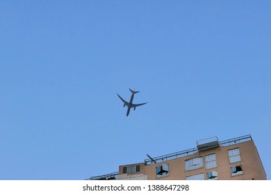 Airplane flying low on the building and sklyline