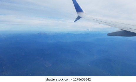 airplane flying with mountains and landscape and clouds
