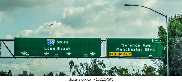 Airplane flying over 405 freeway sign in Los Angeles, California