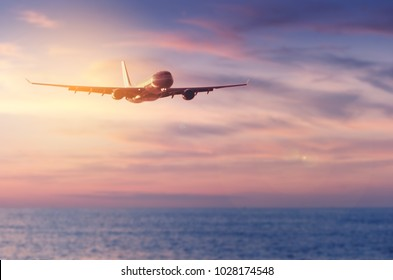 Airplane flying over blur tropical beach and sunset sky abstract background.Copy space of business summer vacation and travel adventure concept.Vintage tone filter effect color