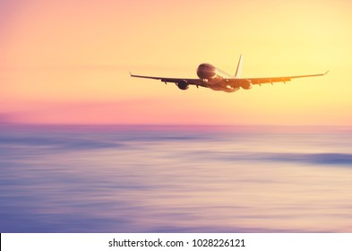 Airplane flying over blur tropical beach with smooth wave and sunset sky abstract background. Copy space of business summer vacation and travel adventure concept. Vintage tone filter effect color.