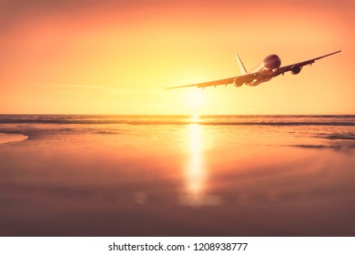Airplane flying over blur tropical beach bokeh sun light wave and sunset sky abstract background. Copy space of business summer vacation and travel adventure concept. Vintage tone filter effect color.