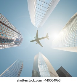An airplane flying over a business center filled with skyscrapers - successful business concept