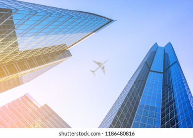 Airplane flying over business skyscrapers, high-rise buildings. Sun light