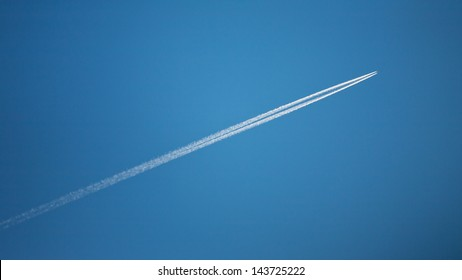An airplane flying over a clear blue sky with long white contrails (condensation or vapor trails) behind it.