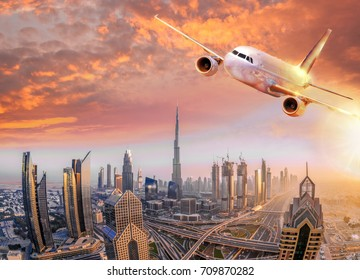 Airplane is flying over Dubai against colorful sunset in United Arab Emirates