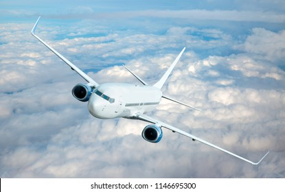 An airplane is flying over low clouds with blue sky