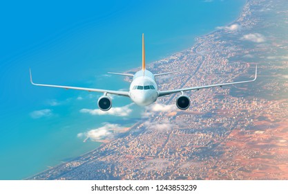 An airplane is flying over low clouds and city with blue sea