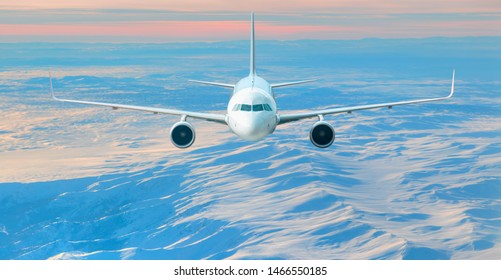 Airplane is flying over low clouds and snowy mountains
