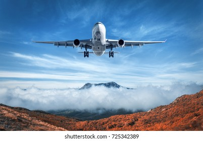 Airplane is flying over low clouds and mountains with autumn forest. Amazing landscape with passenger airplane, trees, mountains, blue cloudy sky. Passenger aircraft. Business travel. Commercial plane