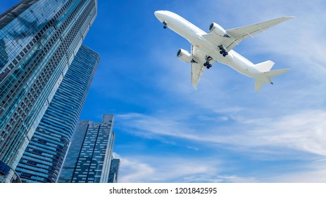 Airplane flying over modern building in the city on blue sky and white cloud with copy space