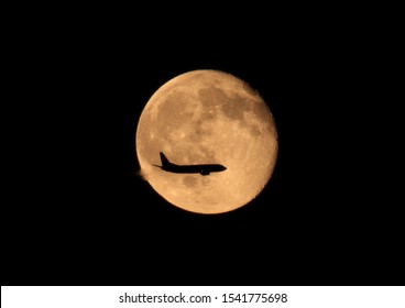 airplane flying over the moon