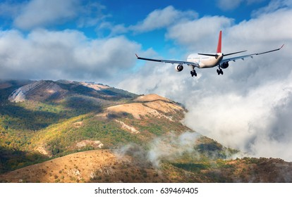 Airplane flying over the mountains. Landscape with white passenger airplane, hills, green forest and big white clouds at sunset. Passenger airliner is landing. Business trip. Commercial aircraft