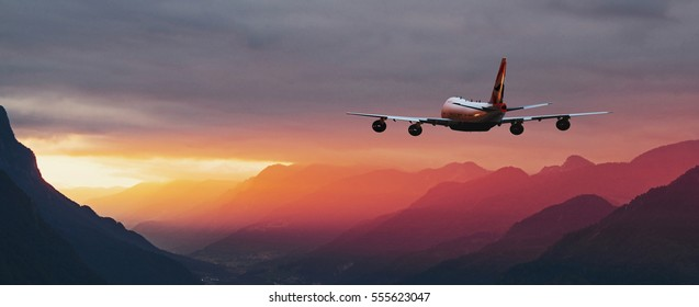 airplane flying over the mountains at sunset