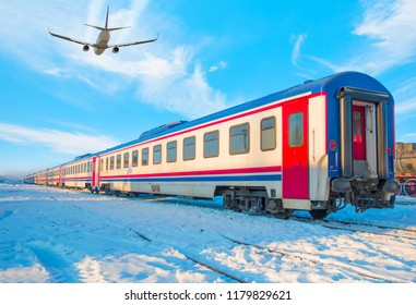 Airplane flying over the red passenger train - Red passenger diesel train moving at the terminal. Snow covered railway tracks - East express between Ankara and Kars - Turkey