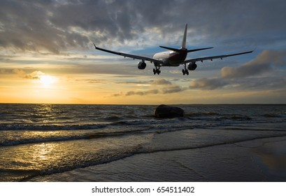 Airplane flying over the sea at sunset time