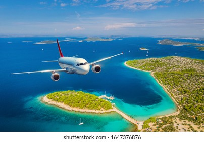 Airplane is flying over small islands and sea at sunny day in summer. Aerial view of passenger airplane, tropical seashore, mountains with green trees, sky and blue water. Top view of aircraft. Travel