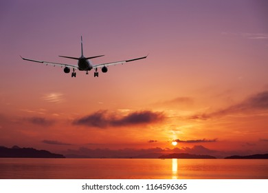 Airplane flying over tropical sea at beautiful sunset or sunrise scenery background,Beautiful sweet purple color scenery view of seascape in phuket thailand