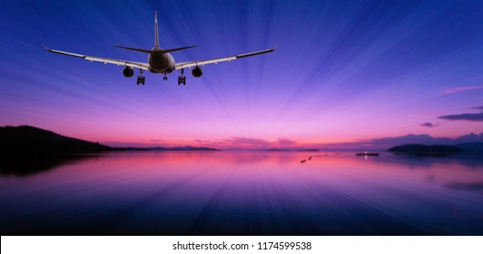Airplane flying over tropical sea at beautiful light sunset or dramatic sky sunrise scenery background.