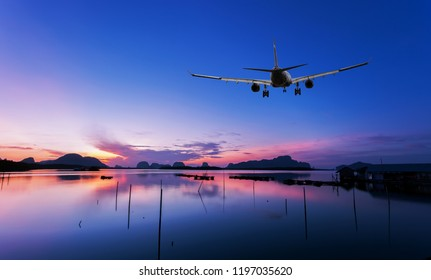 Airplane flying over tropical sea at beautiful sunset or sunrise scenery background