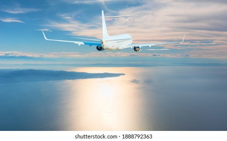 Airplane flying over tropical sea at sunset