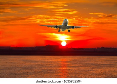 Airplane flying in rays sunrise over water on city background
